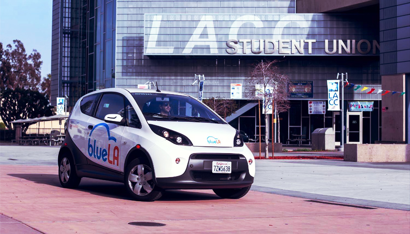 A BlueLA electric car drives past the LACC Student Union building