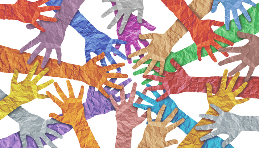 Multicolored paper hands reaching toward the center