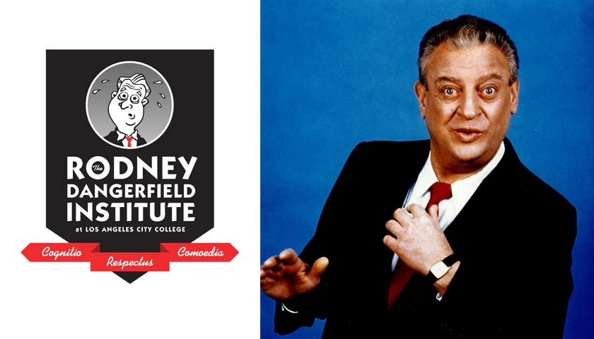 Comedian Rodney Dangerfield in his trademark black suit and red tie.