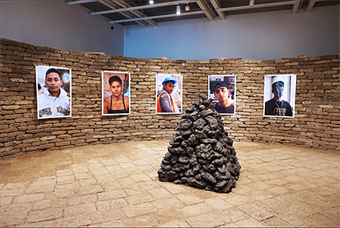 Installation, photos of men are hung on a wall built of rough bricks.