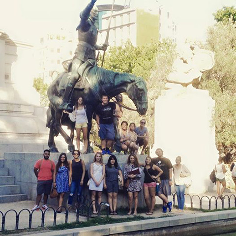 Students pose in front of a statue of Don Quixote