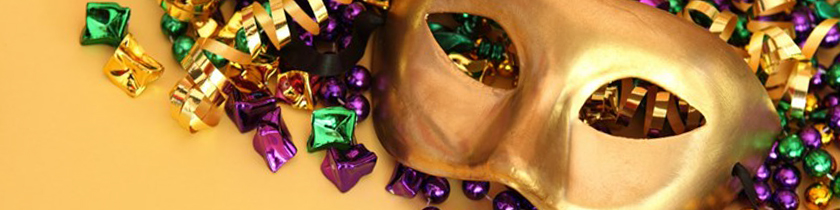 A gold Mardi Gras mask surrounded by gold, green, and purple beads and streamers.