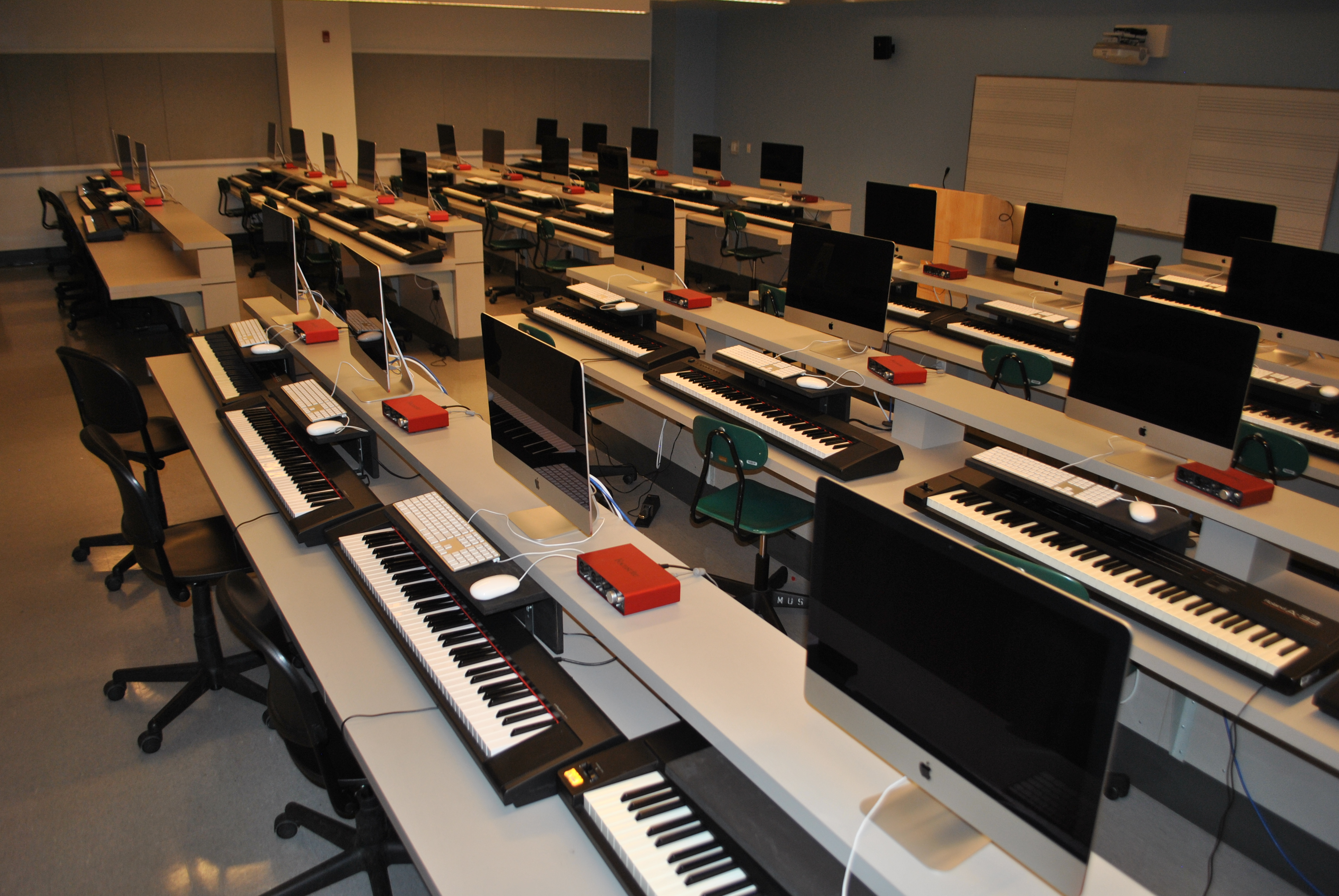 Several rows of stations equipped with MIDI keyboards, audio interfaces, and iMac computers, with a white board in front of the room.