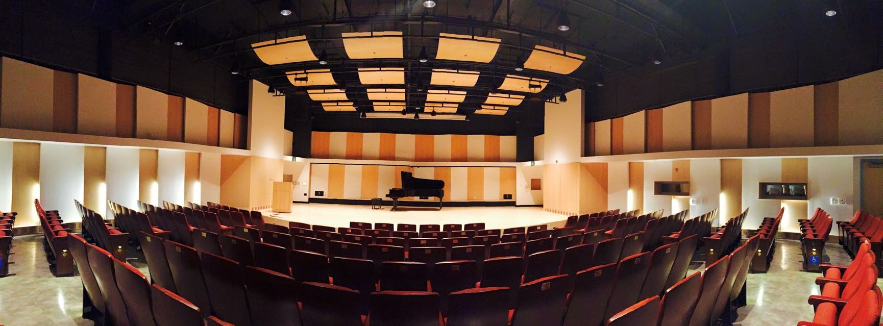 Panoramic view of the Recital Hall. A piano sits on stage with a podium on the left.
