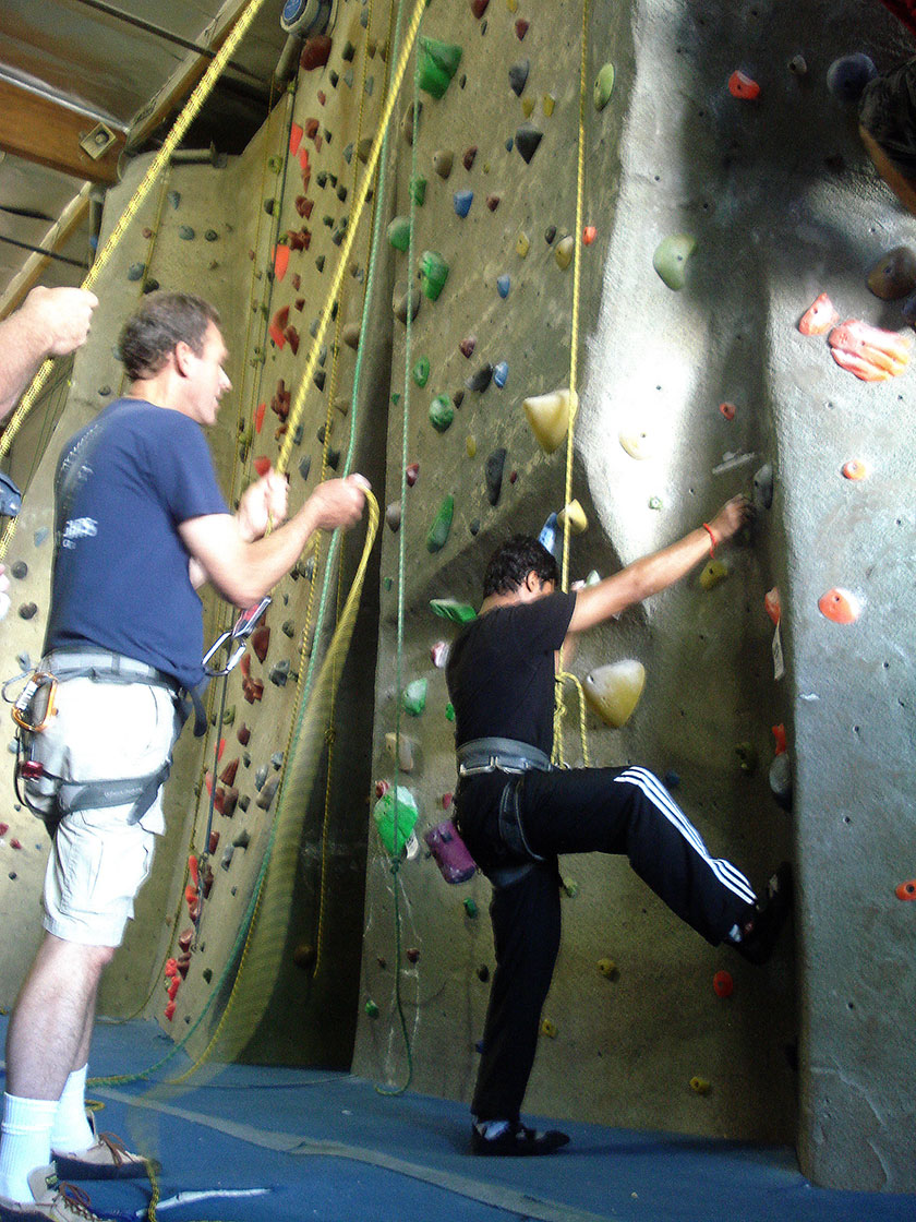 faculty mentor encouraging a student at an indoor climbing event