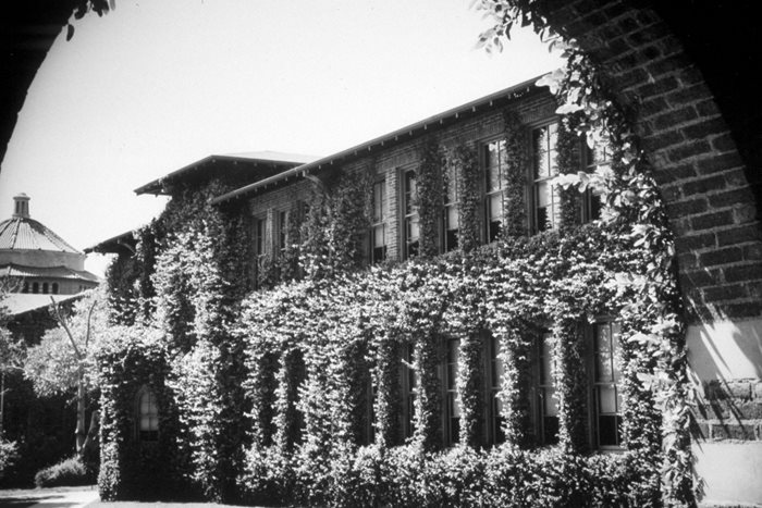 An original LACC building, with large brick archways and ivy covered walls.